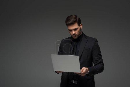stylish businessman holding laptop isolated on grey