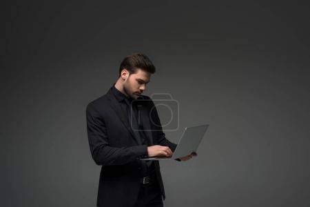 Side view of businessman typing on laptop isolated on grey