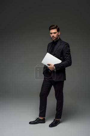 Photo pour Homme d'affaires élégant permanent avec portable sur fond gris - image libre de droit