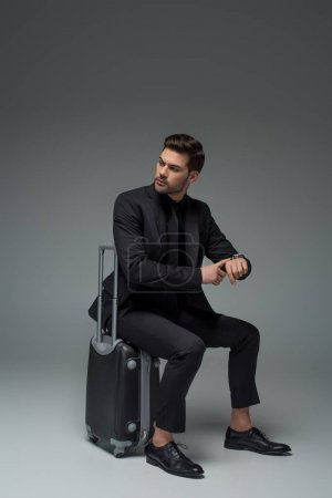 Photo for Business tourist sitting on suitcase and pointing at wristwatch on grey - Royalty Free Image