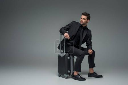 Young business tourist sitting on wheel suitcase on grey