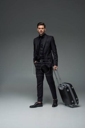 Young stylish tourist carrying suitcase on grey