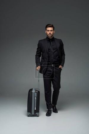 Front view of business tourist carrying cuitase on grey