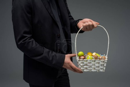 Partial view of male hands holding basket with fruits isolated on grey
