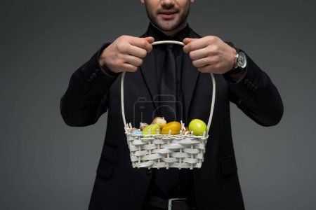 Cropped view of businessman holding basket with fruits isolated on grey