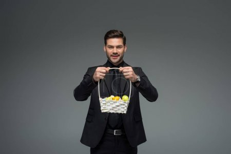 Smiling businessman holding basket with fruits isolated on grey
