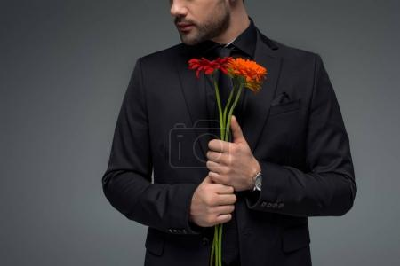 Cropped view of male with bouquet of flowers isolated on grey, international womens day concept