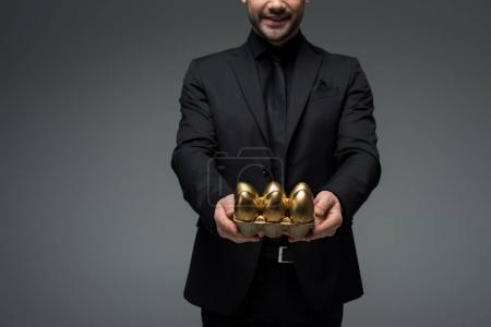 Cropped view of stylish man with golden eggs isolated on grey, easter concept