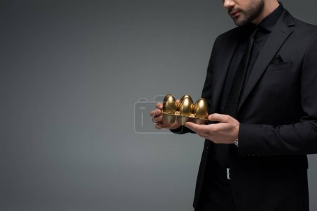 Cropped image of male holding golden eggs isolated on grey, easter concept