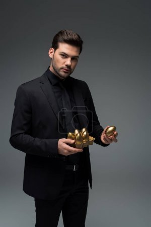 Portrait of male holding golden eggs isolated on grey, easter concept