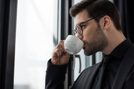 Photo for Side view of businessman in glasses drinking coffee - Royalty Free Image