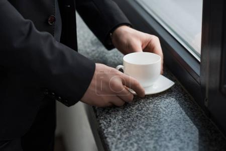 Partial view of businessman holding cup of coffee on window sill