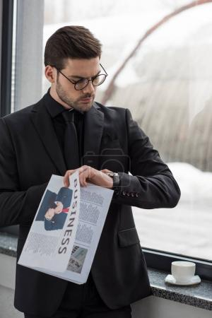 Photo for Young businessman in glasses looking at wristwatch and holding newspaper - Royalty Free Image