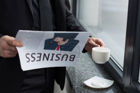 Partial view of businessman reading newspaper and holding coffee cup