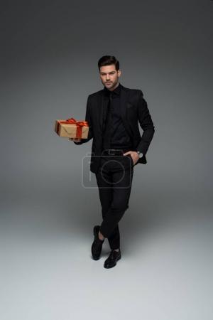 Photo pour Homme en costume noir officielle, tenant la boîte-cadeau sur la notion de jour womens gris, international - image libre de droit