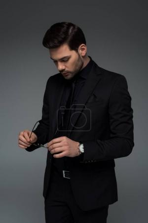 Stylish man in black suit holding glasses isolated on grey