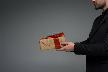 Cropped view of male holding gift box isolated on grey, international womens day concept