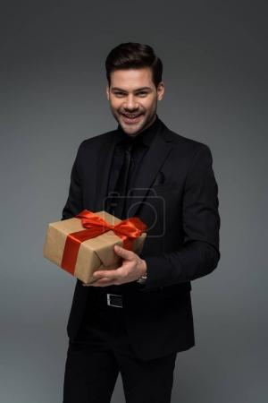 Young smiling male in formal suit holding gift box isolated on grey, international womens day concept
