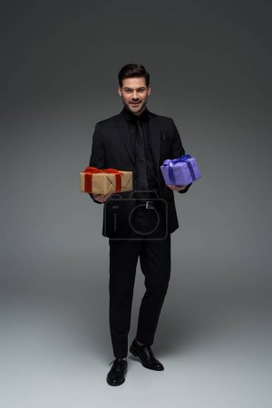 Smiling young man in suit holding two gift boxes on grey, international womens day concept