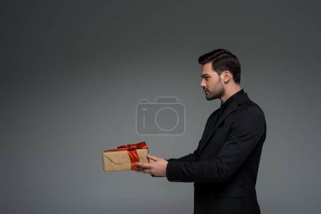 Side view of stylish man holding gift box isolated on grey, international womens day concept