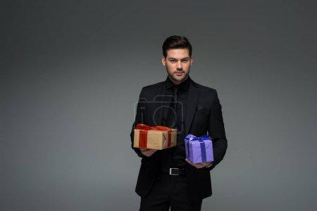 Photo pour Jeune homme tenant deux coffrets cadeaux isolés sur la notion de jour womens gris, international - image libre de droit