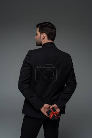 Rear view of stylish man holding gift box isolated on grey, international womens day concept