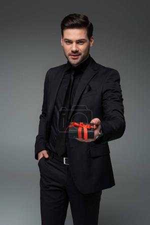 Smiling man in black suit holding gift box isolated on grey, international womens day concept