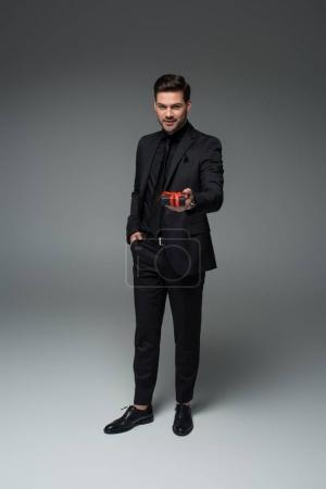 Young stylish man in formal suit holding gift box on grey, international womens day concept