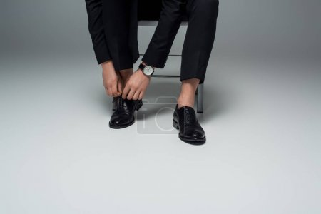 Photo for Partial view of stylish man tying shoelaces on grey - Royalty Free Image