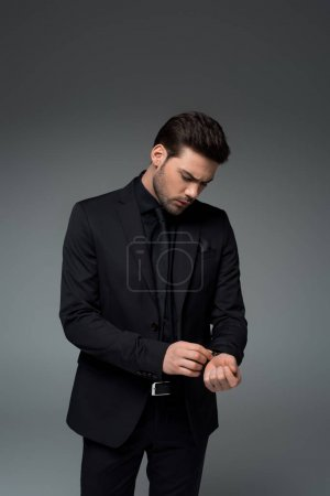 Stylish male in suit correcting wristwatch isolated on grey