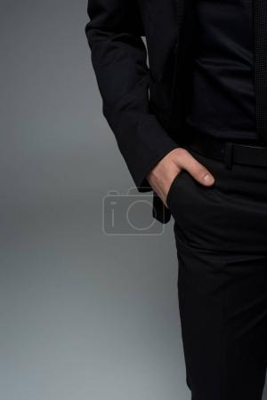 Photo for Partial view of male hand in pocket of black suit isolated on grey - Royalty Free Image