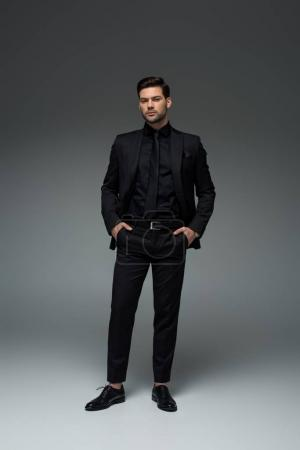 Man in stylish black suit standing with fingers in pockets on grey