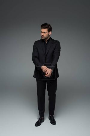 Photo for Stylish man in black suit correcting his wristwatch on grey - Royalty Free Image