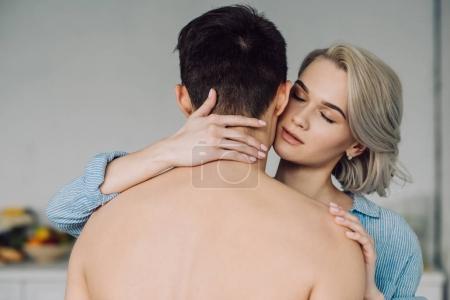 passionate girlfriend hugging shirtless boyfriend at kitchen