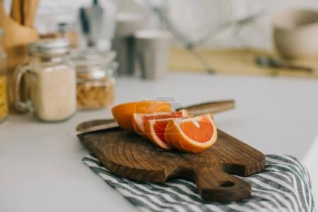 cut grapefruit with knife on cutting board in kitchen