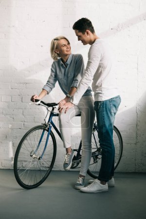 Photo pour Petite amie assise sur le vélo dans le salon et regardant petit ami - image libre de droit