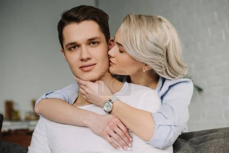 attractive girlfriend kissing boyfriend at home