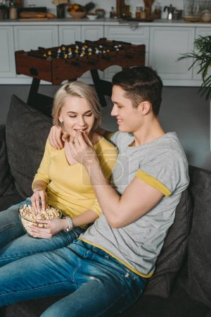 boyfriend feeding girlfriend with popcorn at home