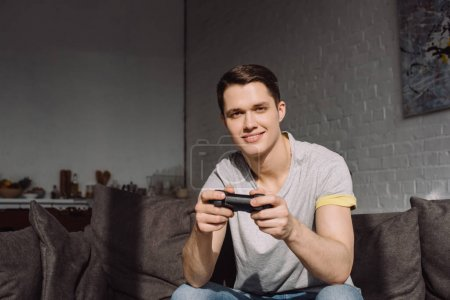 smiling handsome man holding joystick and looking at camera