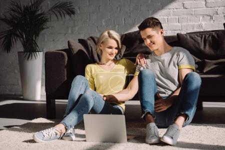 Photo pour Couple assis sur le sol et regarder le film sur l'ordinateur portable dans le salon - image libre de droit