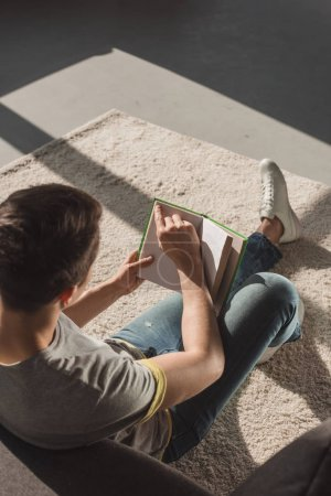 high angle view of man reading book at home