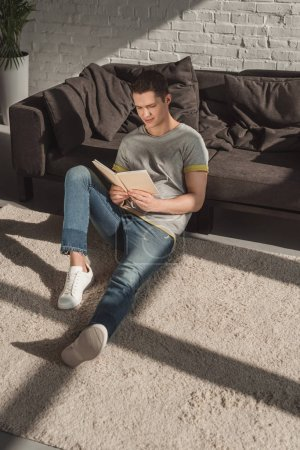 handsome man reading book on floor at home