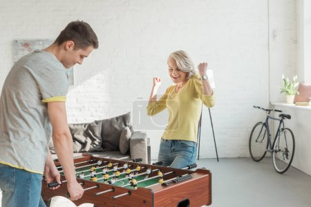 girlfriend showing yes gesture when winning table football game