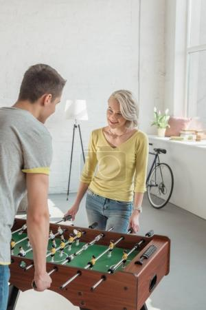 happy couple playing foosball at home