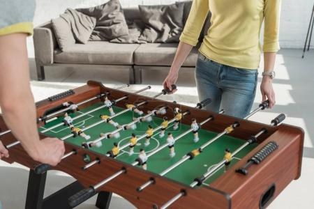 cropped image of couple playing table football at home