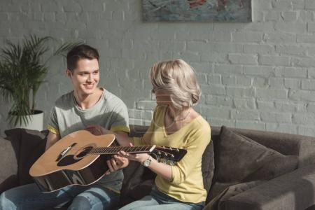 Photo for Smiling boyfriend giving acoustic guitar to girlfriend at home - Royalty Free Image