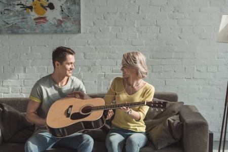 Photo for Boyfriend giving acoustic guitar to girlfriend at home - Royalty Free Image
