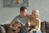 "Постер, картина, фотообои ""бойфренд игры на акустической гитаре и глядя на подругу на дому"""