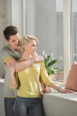 boyfriend hugging girlfriend near windowsill at home