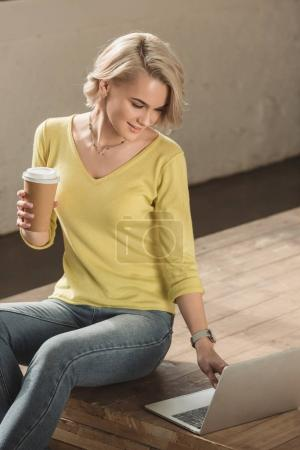 attractive girl holding coffee in paper cup and using laptop at home